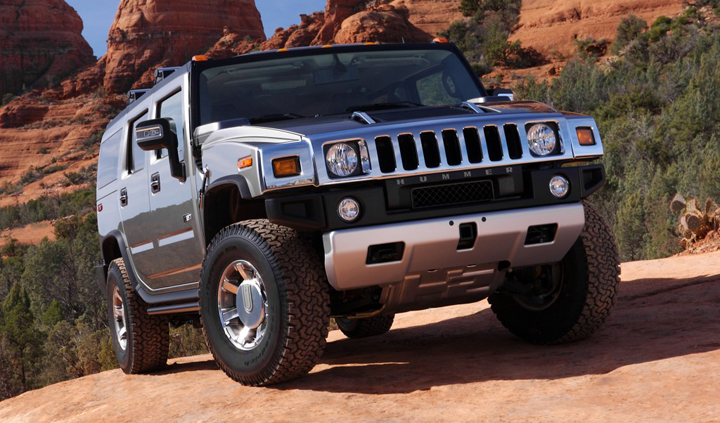 A silver Hummer H2 drives over a rocky hill